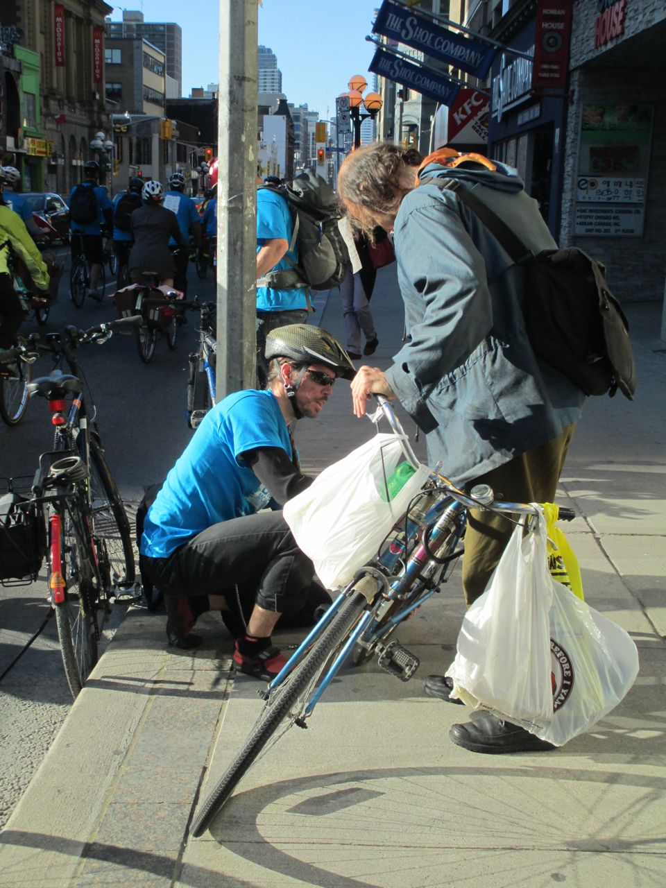 A cyclist helps repair a bike